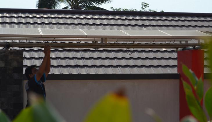 Seorang teknisi tengah melakukan pengecekan panel surya di SMKN 1 Karimunjawa